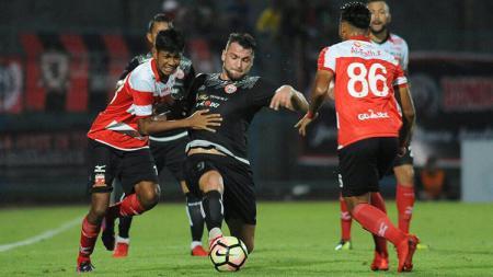 Striker Persija, Marko Simic, di tengah penjagaan pemain Madura United. - INDOSPORT