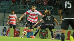 Indosport - Pemain Madura United, Nuriddin Davronov saat mengontrol bola.