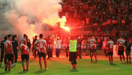Para pemain Madura United memberi salam hormat disertai flare dari suporter Madura.
