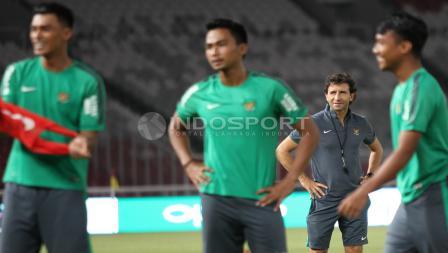 Pelatih Luis Milla (belakang) tersenyum mengamati para pemainnya berlatih.