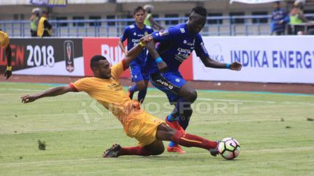 Marco Sandy (Sriwijaya FC) berusaha menggagalkan aksi Ezechiel N'Douassel. - INDOSPORT