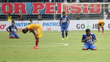 Para pemain Persib Bandung dan Sriwijaya FC tertunduk setelah pluit panjang ditiup. Herry Ibrahim - INDOSPORT