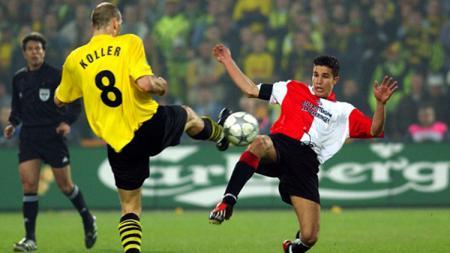 Robi van Persie (kiri) sedang berebut bola dengan pemian Dortmund, Jan Koller. - INDOSPORT