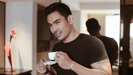 Robby Purba sedang menikmati secangkir kopi. - INDOSPORT