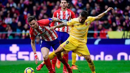 Cristian Portugues (kanan) tampak menjegal Saul Niguez (kiri) yang tengah berusaha mengambil bola. - INDOSPORT