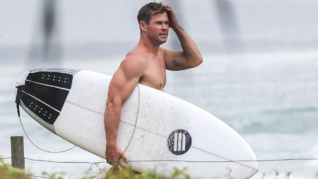 Chris Hemsworth saat hendak berselancar. - INDOSPORT