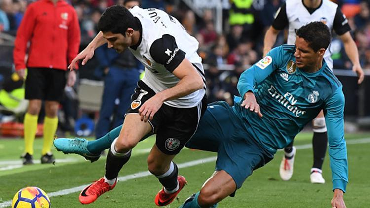 Raphael Varane (kanan) berebut bola dengan pemain Valencia. Copyright: INDOSPORT
