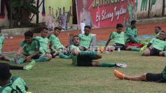Indosport - Oktavio Dutra (tengah) saat memimpin teman-temannya, pendinginan. Seusai latihan terakhir di lapangan Polda Jatim.