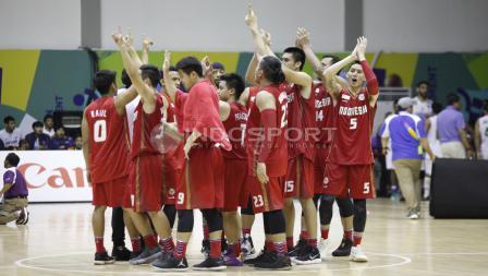 Timnas Basket Indonesia melakukan toss usai menang. Herry Ibrahim/INDOSPORT