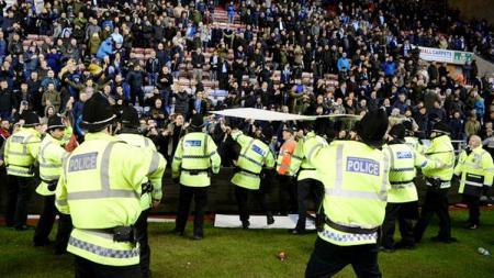 Suporter Wigan Athletic melemparkan papan iklan ke arah polisi atau ke dalam lapangan. - INDOSPORT