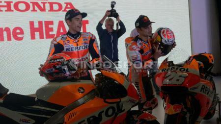 Marc Marquez dan Dani Pedrosa membuka helm yang mereka gunakan. - INDOSPORT