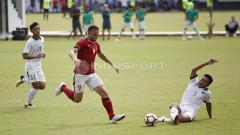 Indosport - Ilija Spasojevic (tengah) berupaya melewati hadangan bek Timnas U-19, Nurhidayat Haji Haris.