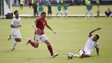 Ilija Spasojevic (tengah) berupaya melewati hadangan bek Timnas U-19, Nurhidayat Haji Haris.