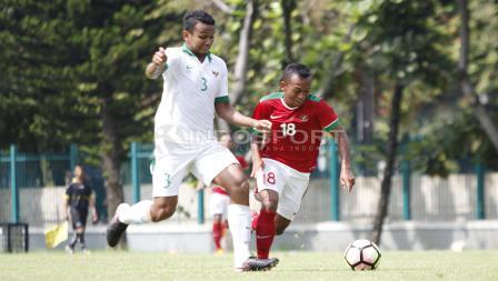 Irfan Jaya (kanan) berhasil melewati hadangan pemain Timnas U-19.