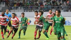 Indosport - Situasi pertandingan Persebaya vs Madura United.