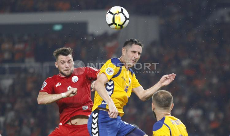 Marko Simic melakukan duel udara dengan salah satu pemain Tampines Rovers. Copyright: Herry Ibrahim/INDOSPORT