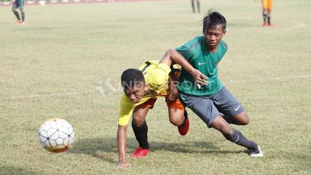Pemain Academy Babek (kiri) berusaha keras menghalangi pergerakan pemain Timnas U-16.
