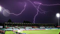 Indosport - Ilustrasi sambaran petir di stadion sepakbola.