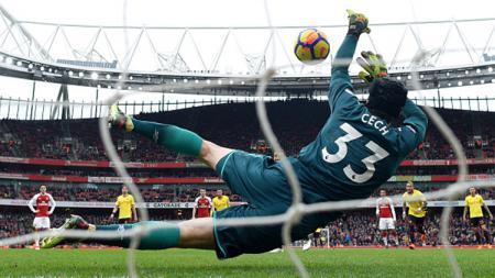 Peter Cech menepis tendangan penalti pemain Watford, Troy Deeney. - INDOSPORT
