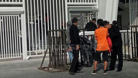 Keamanan setempat memerikas Jakmania yang akan memasuki stadion. - INDOSPORT