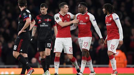 Kebahagian wajah pemain Arsenal dan tertunduknya wajah pemain AC Milan. - INDOSPORT