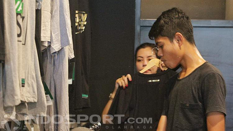 Keluarga Sudirman memilih kaos-kaos. Copyright: INDOSPORT/Fitra Herdian