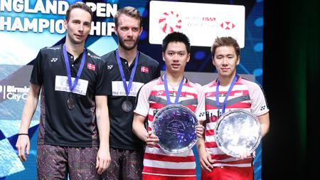Pasangan Kevin/Marcus foto bersama dengan pasangan Denmark Boe/Mogensen di podium juara All England. - INDOSPORT
