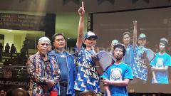 Indosport - Yuli Sumpil, dirijen Aremania menyerahkan bantuan hasil dari iuran sukarela Aremania dengan nilai Rp 31 juta