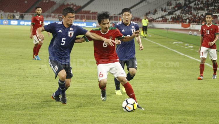 Muhammad Iqbal (tengah) dikawal ketat dua pemain Jepang. Copyright: Abdurrahman Ranala/INDOSPORT