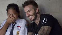 Indosport - Tawa canda David Beckham dengan salah seorang anak pelajar.