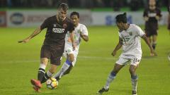Indosport - Wiljan Pluim (kiri) dalam bayang-bayang dua pemain Persela Lamongan.