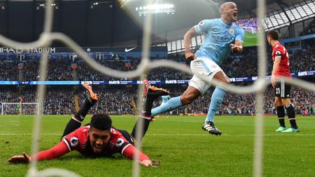 Bek tengah sekaligus kapten Man United, Chris Smalling (kiri) dan Vincent Kompany, bek tengah sekaligus kapten Man City. - INDOSPORT