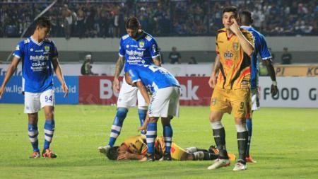 Salah satu pemain Mitra Kukar terdampar di tanah setelah kalah adu body dengan pemain Persib. - INDOSPORT