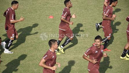 Para pemain Persija melakukan pemanasan sebelum melakukan latihan.