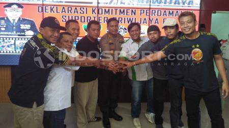 Para pendukung Sriwijaya FC mengukuhkan aksi perdamaian. - INDOSPORT