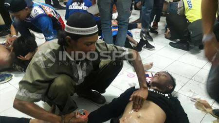 Evakuasi penonton yang menjadi korban atas kerusuhan laga Arema vs Persib. - INDOSPORT