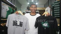 Indosport - Firman menunjukkan dua kaus hasil desainnya.
