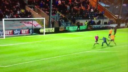Pemain Oldham Athletic AFC menhentikan penyusup lapangan yang hendak menyerang wasit. - INDOSPORT