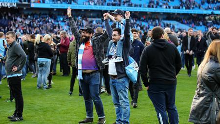 Para pendukung Man City turun ke lapangan merayakan kemenangan. . - INDOSPORT