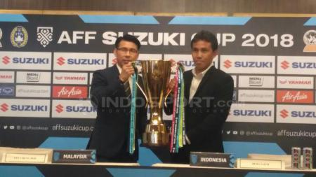 Pelatih Timnas Malaysia, Tan Cheng Hoe mengangkat trofi dengan Bima Sakti. - INDOSPORT