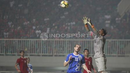 Kiper Indonesia, Awan Setho mengamankan bola dari serangan Uzbekistan. Herry Ibrahim