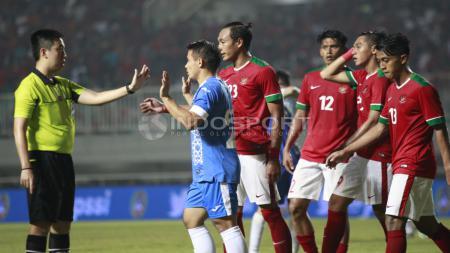 Wasit asal Hongkong, Luk Kin Sun mencoba mengambil keputusan atas insiden Hargianto dengan pemain Uzbekistan. Herry Ibrahim - INDOSPORT