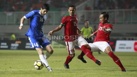 Hansamu Yama mencoba menghalau aksi pemain Uzbekistan, Amonov Azizbek. Herry Ibrahim
