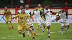 Indosport - Pemain PS Tira, Pandi Lestaluhu menghalau bola yang mengarah ke arah pertahanan tim nya.