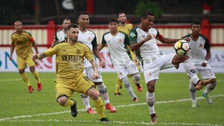 Pemain PS Tira, Pandi Lestaluhu menghalau bola yang mengarah ke arah pertahanan tim nya.