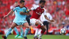 Indosport - Pemain Arsenal dan Burnley saling merebut bola