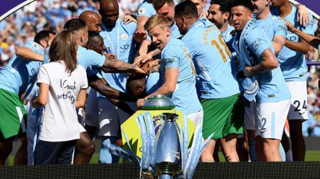 Reaksi Pemain Man City saat melihat trofi Liga Primer Inggris terjatuh. - INDOSPORT