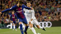 Indosport - Gerard Pique (kiri) menjaga penguasaan bola dari kejaran Ronaldo.