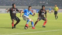 Indosport - Jonathan Bauman (tengah) dalam pengawalan ketat dua pemain Persipura.