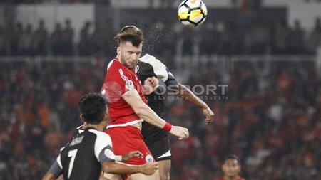Marko Simic berduel udara dengan pemain Home United/. - INDOSPORT